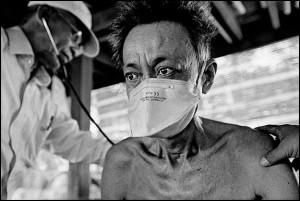 A man with TB is examined during a home visit by a medical worker with the NGO, Cambodian Health Committee, courtesy © James Nachtwey, 2008.