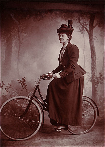 "Photographer unknown, A lady wearing ""proper attire"" astride her bicycle, Circa 1898. Cabinet card, Collection of Lorne Shields."
