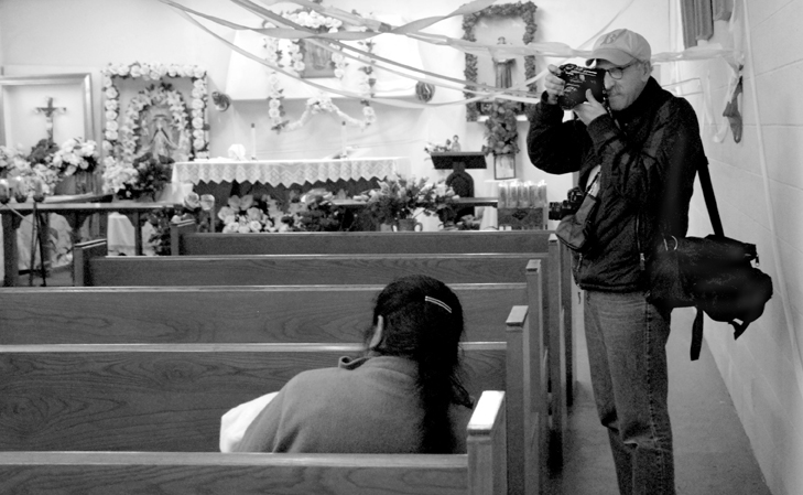 Ken Light in a church photographing the Posada (a Latin American Christmas Festival) in Toneyville during the creation of Valley of Shadows and Dreams. Photo by Allison Light. Courtesy, Ken Light 2007
