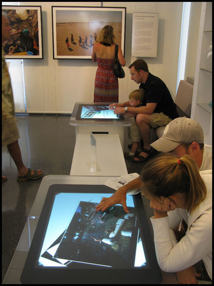 A young family has fun exploring the capabilities of the Microsoft surface table, where you can move, rotate, sort through, and enlarge digital images with the touch of your fingertips. Courtesy © Susan Katz, 2010